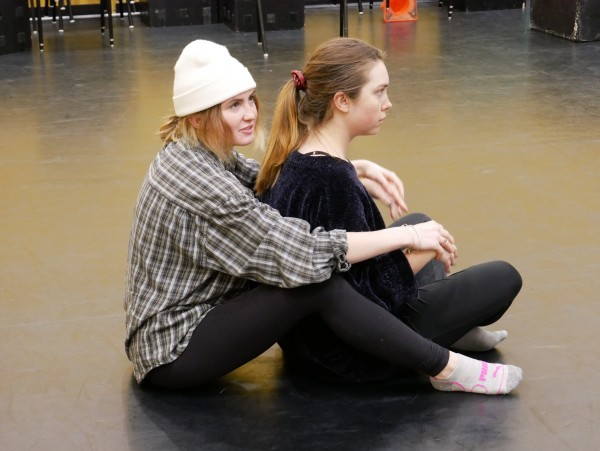A photograph of two women sitting on the floor in profile. One of the women, Leanne sits between the legs of the other woman, Sadie. Leanne faces away from Sadie, with crossed legs and arms floating in front of her. Sadie wraps her arms around Leanna resting her hands on top of hers.